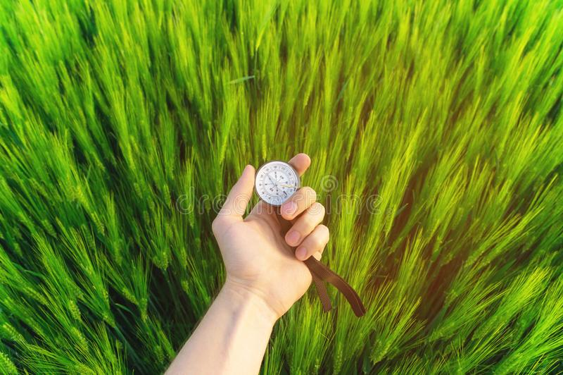 Conclusion d'une direction en nature sur un champ de blé Une main du ` s d'homme tient une boussole photographie stock
