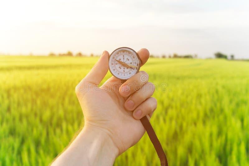 Conclusion d'une direction en nature sur un champ de blé Une main du ` s d'homme tient une boussole photos stock