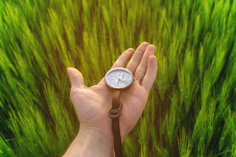 Conclusion d'une direction en nature sur un champ de blé Une main du ` s d'homme tient une boussole image libre de droits