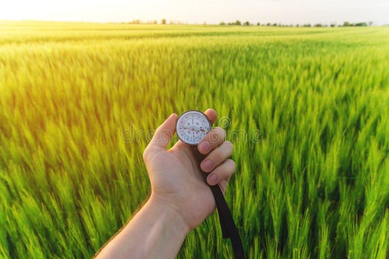 Conclusion d'une direction en nature sur un champ de blé Une main du ` s d'homme tient une boussole images stock
