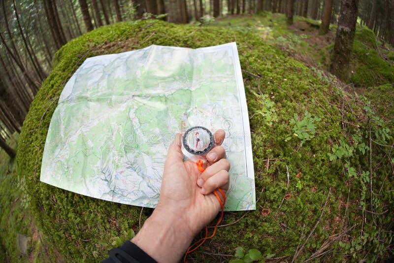 Conclusion de la bonne position dans la forêt avec une carte et une boussole images libres de droits
