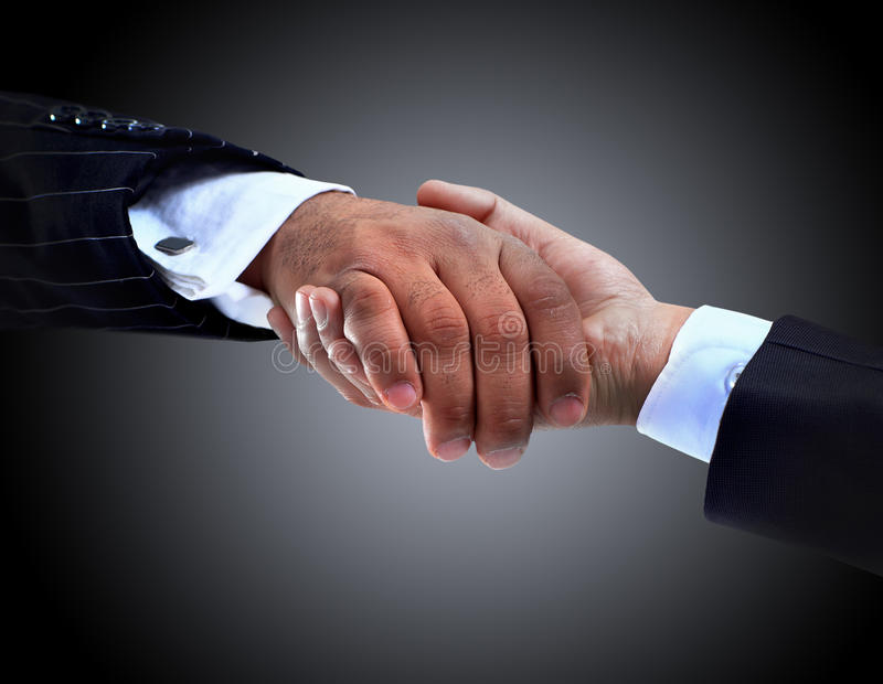 The conclusion of the transaction. Handshake. on a dark background royalty free stock image