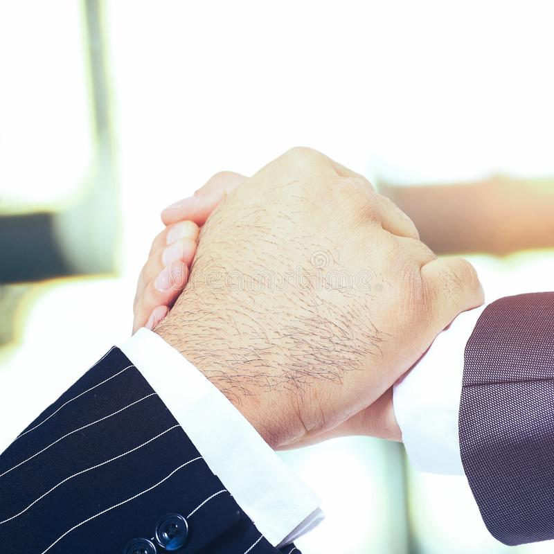 The conclusion of the transaction. Handshake. Make a deal. Handshake on an office background on a sunny day royalty free stock photos