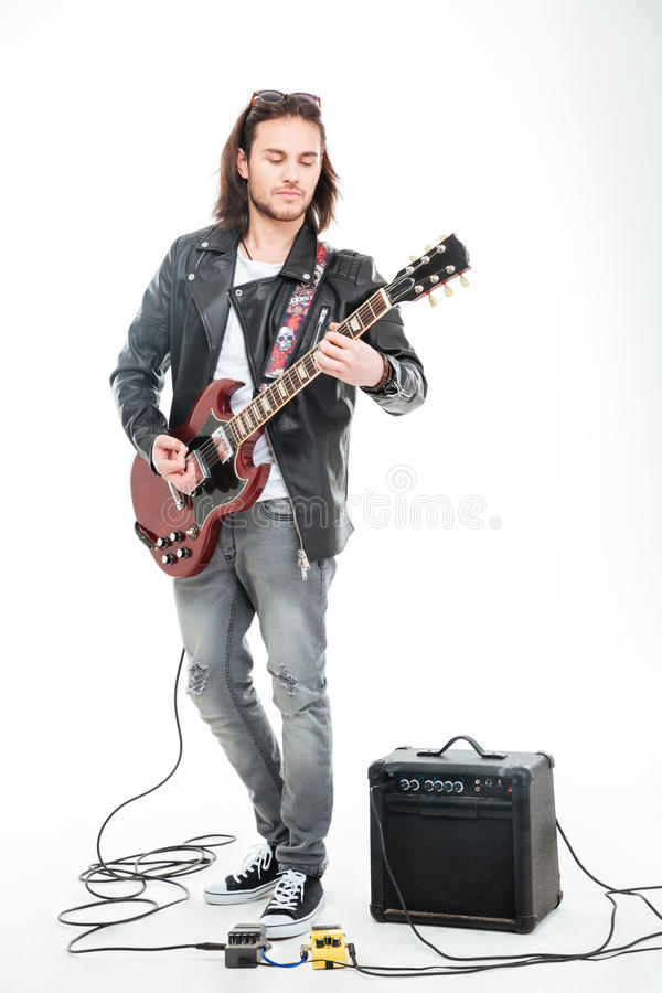 Concntrated young male guitarist playing electric guitar and using amplifier. Over white background stock image