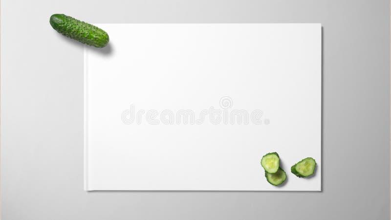 Concombre avec la tranche sur le livre blanc sur le fond propre images stock