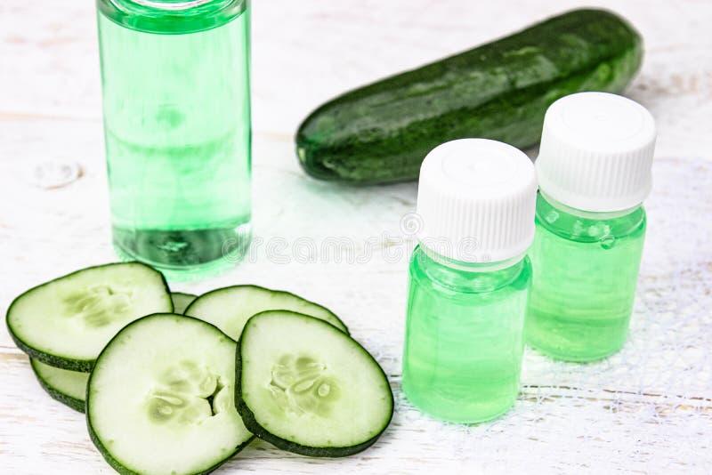 Concombre coupé en tranches et une bouteille d'extrait de concombre Cosmétiques liquides pour des soins de la peau photos stock