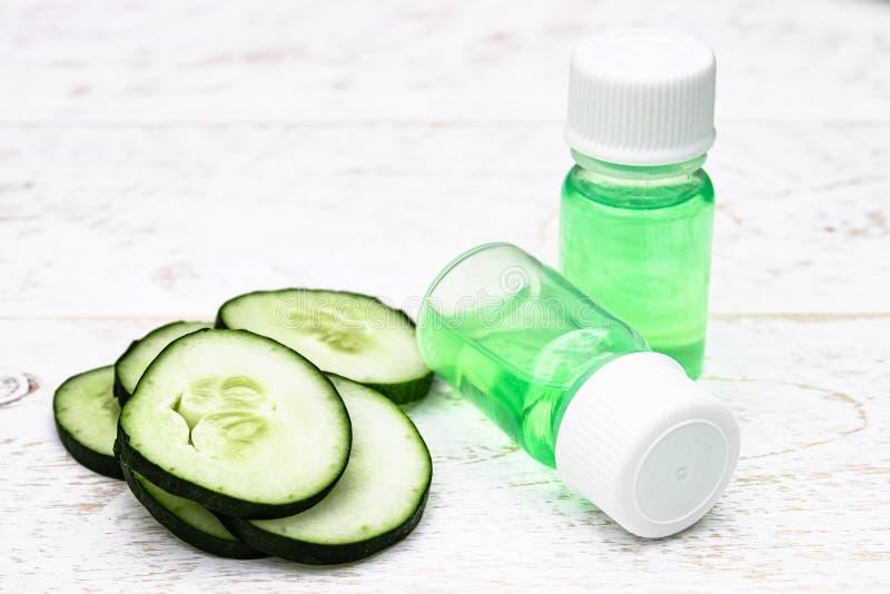 Concombre coupé en tranches et une bouteille d'extrait de concombre Cosmétiques liquides pour des soins de la peau images stock