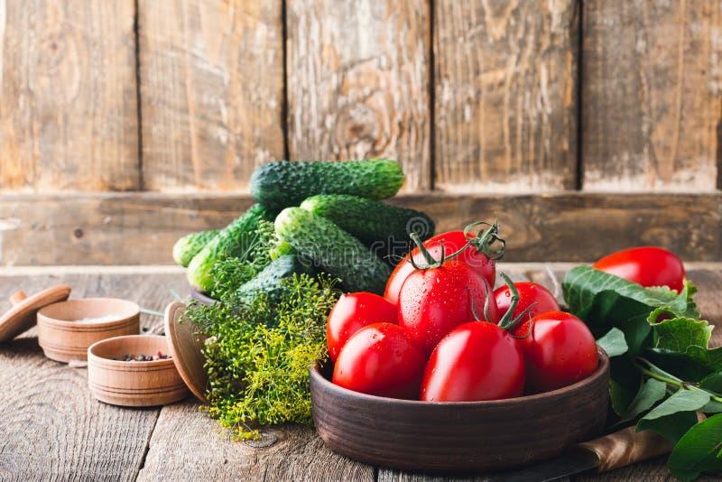 Concombres et tomates organiques mûrs sur la table en bois rustique photos stock