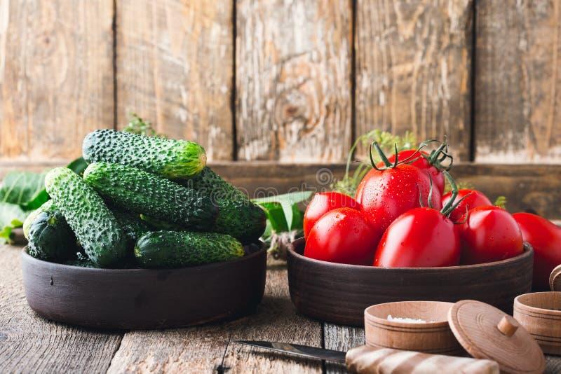 Concombres et tomates organiques mûrs sur la table en bois rustique images libres de droits