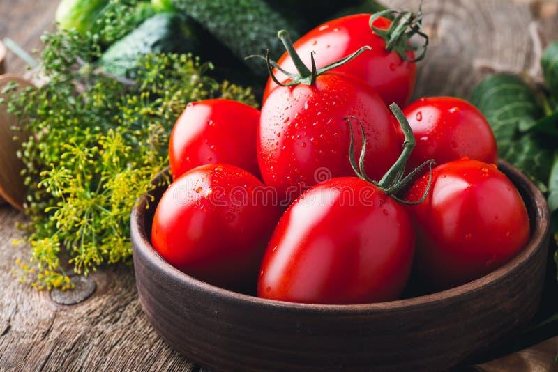 Concombres et tomates organiques mûrs sur la table en bois rustique photo libre de droits
