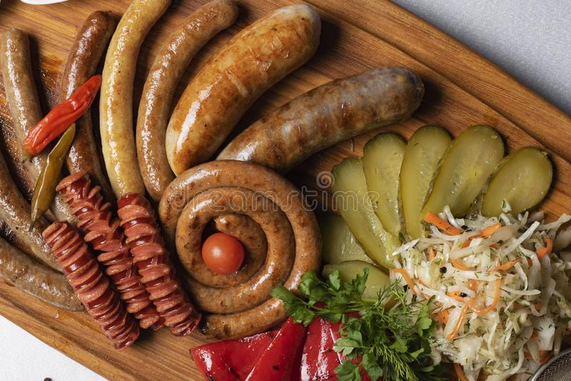 Concombres marinés, saucisses bouillies, fromage avec les tomates frites, persil et cerise dans le restaurant photos libres de droits