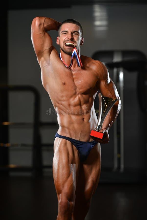 Concorrente maschio di forma fisica che mostra la sua medaglia di conquista fotografia stock