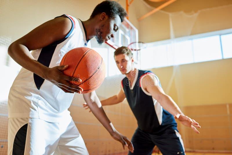 Concorrentes novos que jogam o basquetebol na corte do treinamento foto de stock royalty free