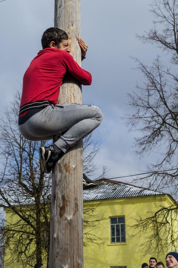 Concorrenza nazionale russa scalando un palo di legno nella celebrazione della conclusione dell'inverno nella regione di Kaluga i fotografie stock