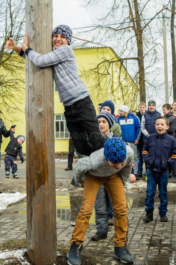 Concorrenza nazionale russa scalando un palo di legno nella celebrazione della conclusione dell'inverno nella regione di Kaluga i fotografia stock