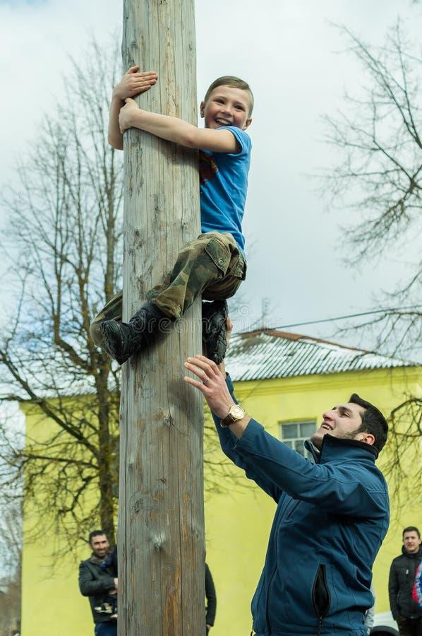 Concorrenza nazionale russa scalando un palo di legno nella celebrazione della conclusione dell'inverno nella regione di Kaluga i immagini stock libere da diritti
