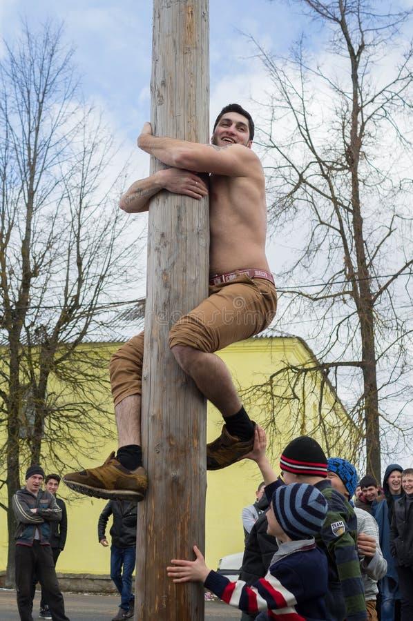 Concorrenza nazionale russa scalando un palo di legno nella celebrazione della conclusione dell'inverno nella regione di Kaluga i immagine stock libera da diritti