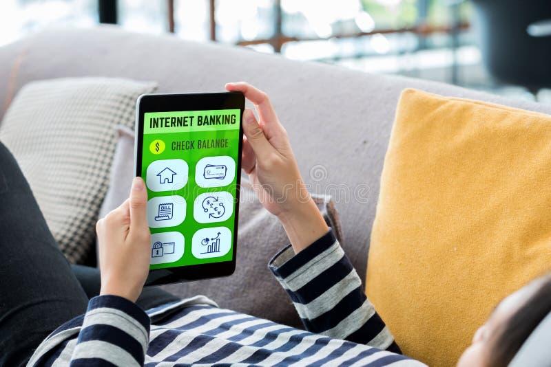 Concpet dos Internet banking Mulher que encontra-se para baixo no sofá usando o app móvel da tabuleta para a fatura pagamento em  imagem de stock royalty free