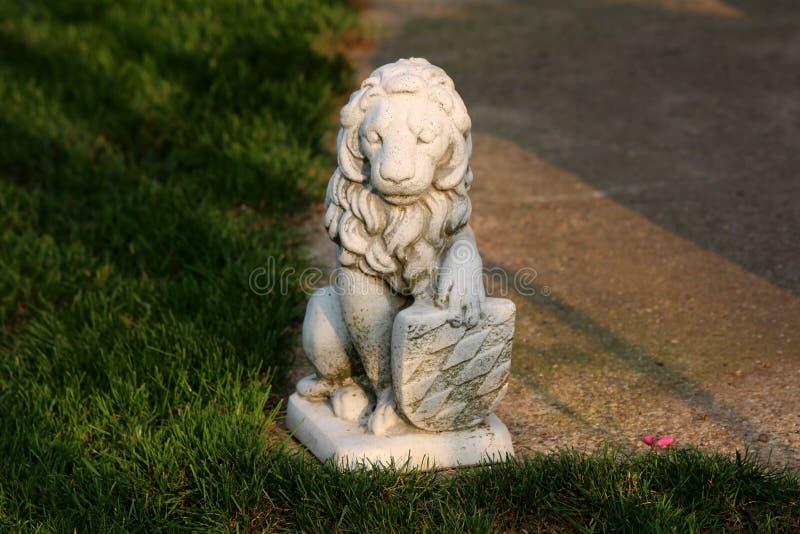 Concreet beeldhouwwerk van het machtige schild van de leeuwholding op rand van concrete weg die met gras op warme zonnige dag wor stock foto