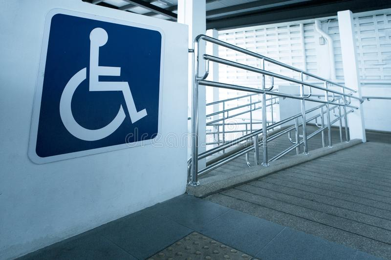 Concret ramp way with stainless steel handrail with disabled sign for support wheelchair disabled people. royalty free stock photos