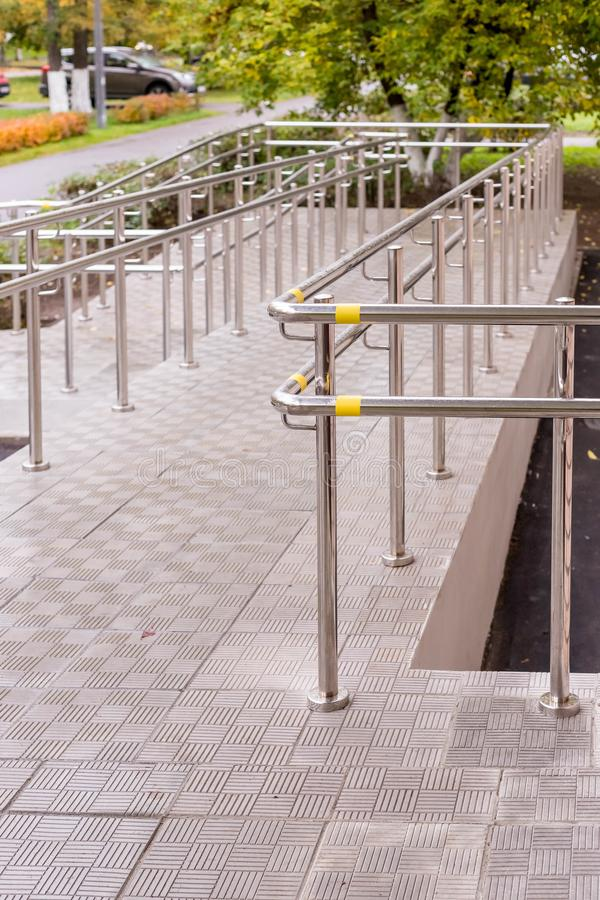 Concret ramp way with stainless steel handrail for support wheelchair disabled people. Health care concept. Copy space stock images