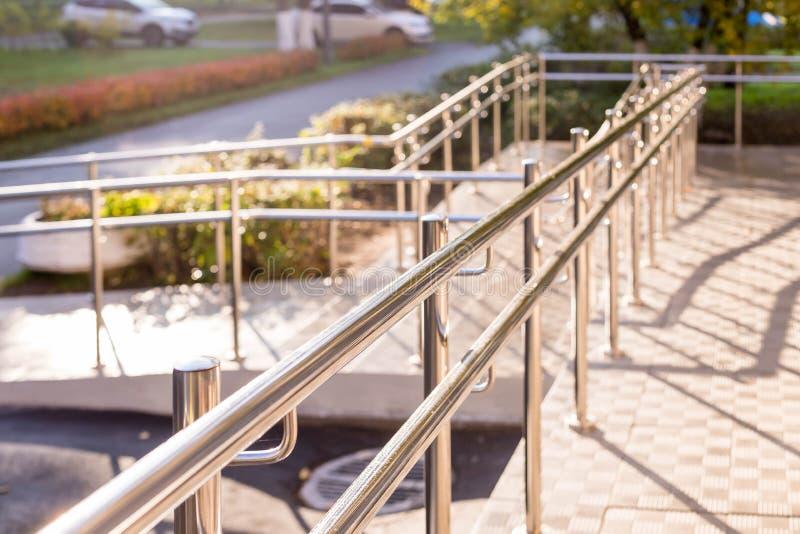 Concret-Rampenweise mit Edelstahlhandlauf mit behindertem Zeichen für Stützrollstuhlbehinderter Sträflinge und Arme lizenzfreies stockfoto