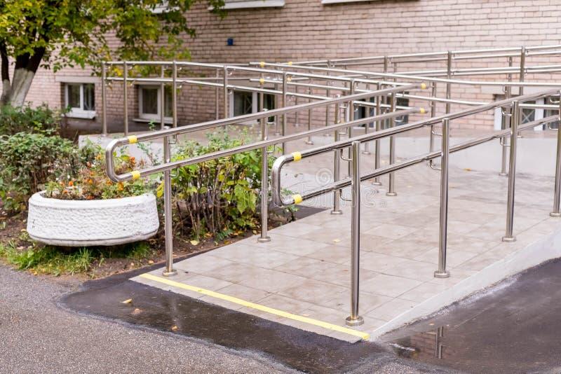 Concret-Rampenweise mit Edelstahlhandlauf mit behindertem Zeichen für Stützrollstuhlbehinderter Sträflinge und Arme stockfotografie