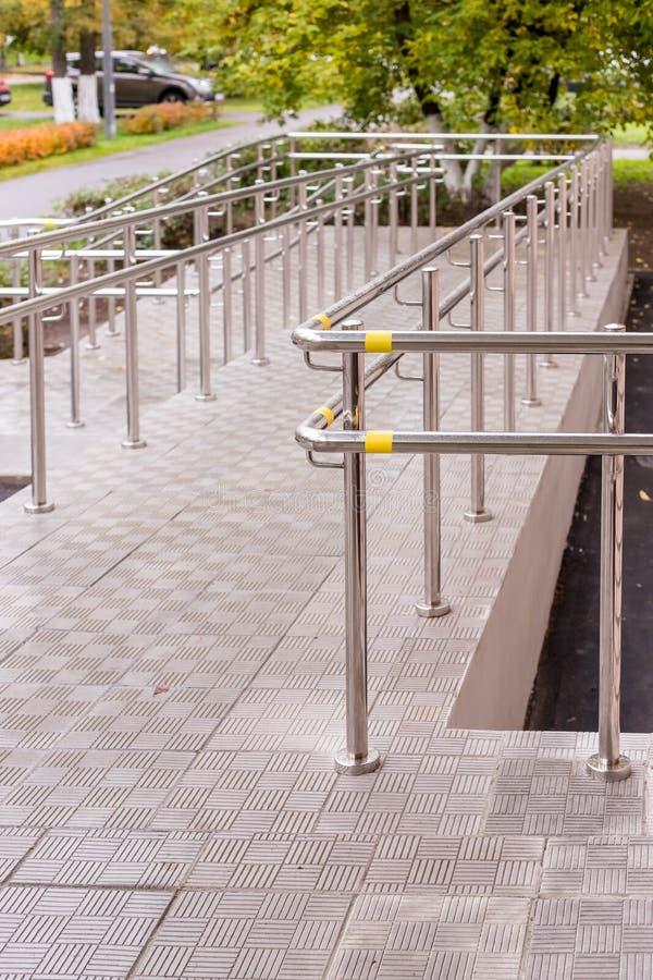 Concret-Rampenweise mit Edelstahlhandlauf für Stützrollstuhlbehinderter Stellen Sie schützende Schablone und die Pille gegenüber, stockbilder