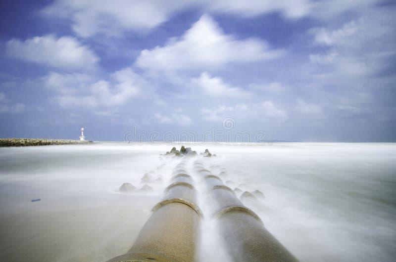 Concrete afvoerkanaalpijpleiding bij kustlijn zachte witte golf die het strand toe te schrijven aan lange blootstelling raken stock afbeeldingen