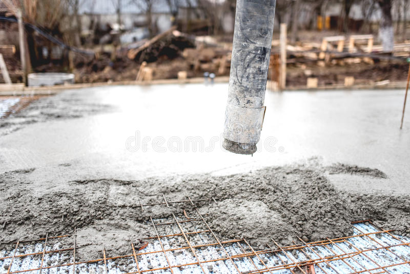 Concrete automatic pump tube working on foundation of construction site. Close up of concrete automatic pump tube working on foundation of construction site stock photos