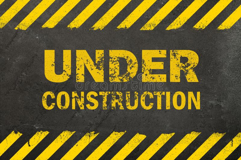 Concrete background with under construction sign royalty free stock photo