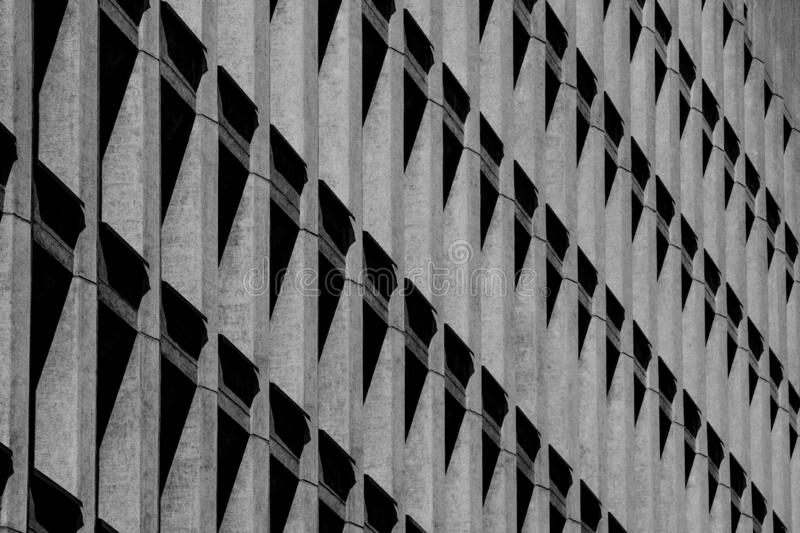 Concrete building with a shadow in the form of triangles in the window openings. Abstraction and architecture stock photo