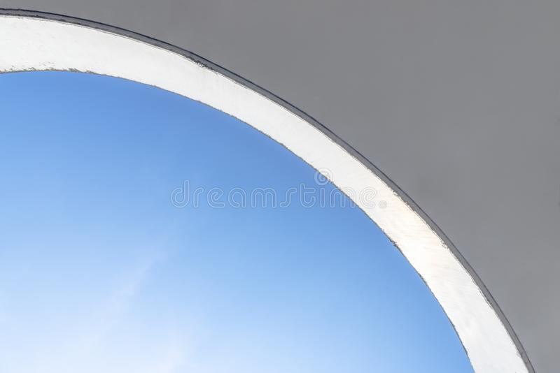 Concrete ceiling and blue sky. Abstract background. Curved concrete ceiling against a blue sky on a sunny day. Architectural abstract background minimalism style stock images