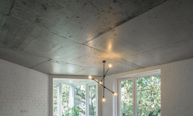 Concrete ceiling and lighting in a modern apartment. Concrete style in the apartment. stock image