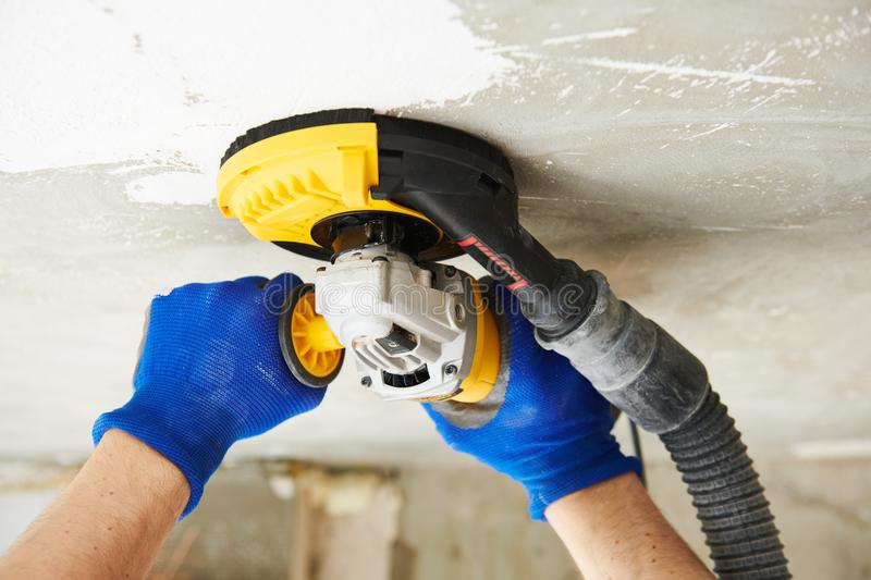 Concrete ceiling surface grinding by angle grinder machine royalty free stock photo