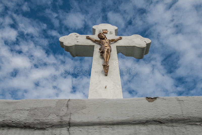 Concrete christian cross with brass Jesus on blue cloudy sky. royalty free stock image