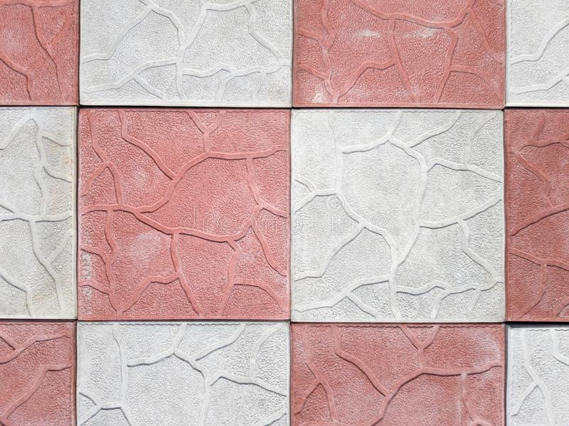 Concrete coating of gray and red colors. Sidewalk of gray and pink pavers close-up. Texture, background from curly gray-orange. Stone. Top view on the sidewalk stock image