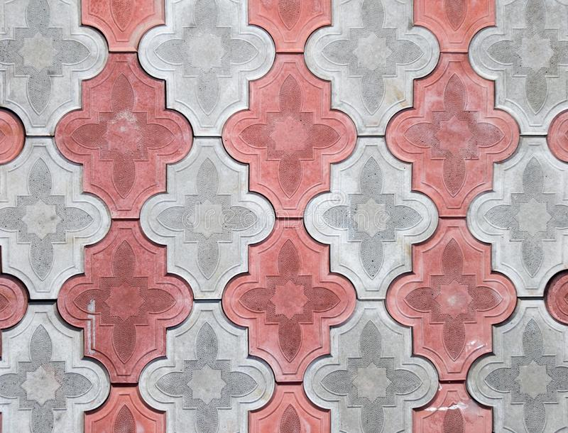 Concrete coating of gray and red colors. Sidewalk of gray and pink pavers close-up. Texture, background from curly gray-orange. Stone. Top view on the sidewalk royalty free stock photography