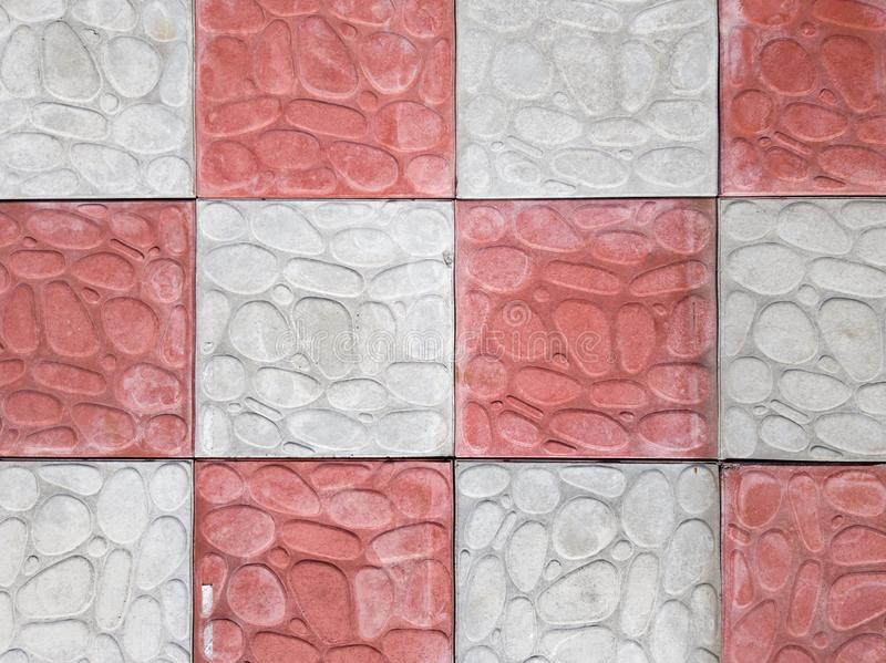 Concrete coating of gray and red colors. Sidewalk of gray and pink pavers close-up. Texture, background from curly gray-orange. Stone. Top view on the sidewalk stock images