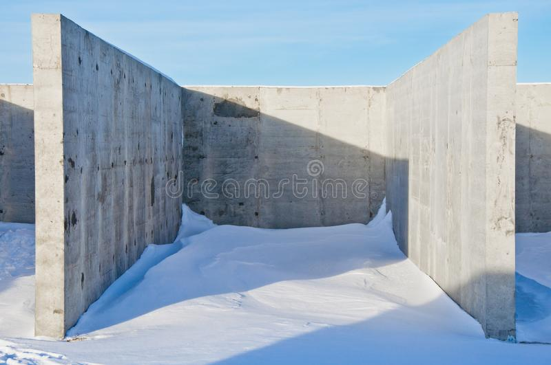 Concrete construction on the background of the winter landscape. Is covered with snow. Frosty sunny day royalty free stock image
