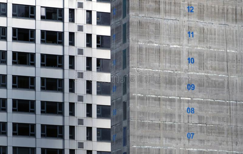 Concrete core of a tall apartment building under construction with floor numbers marked in blue paint with silver cladding on. The concrete core of a tall stock photo