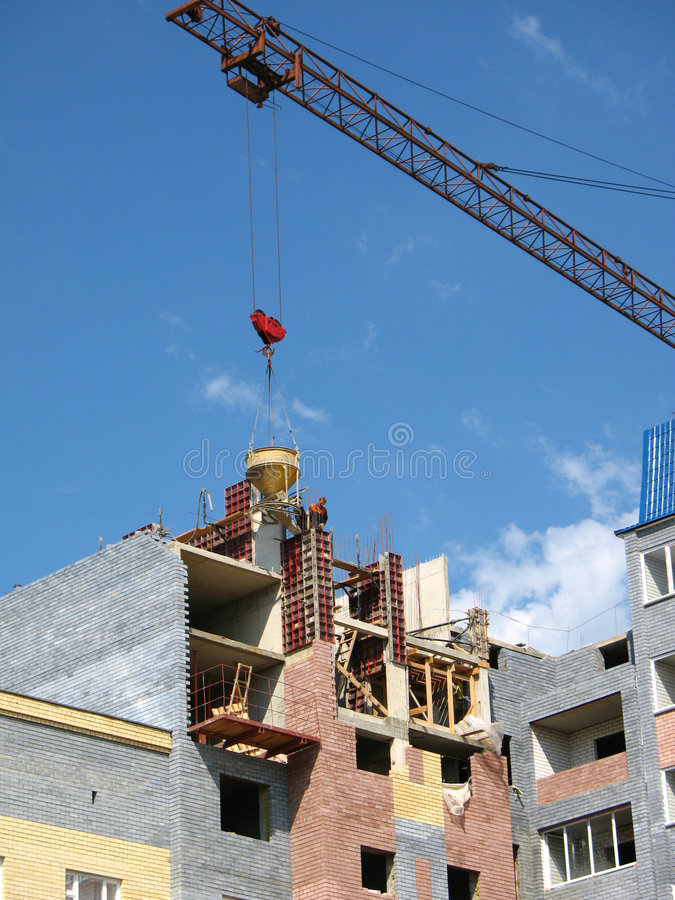 Concrete and crane. Builders put concrete in design of the building by means of crane royalty free stock image