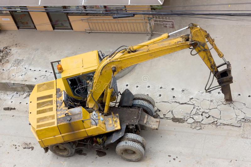 Concrete crusher and hydraulic crushing hammer demolishing reinforced concrete road.  stock image