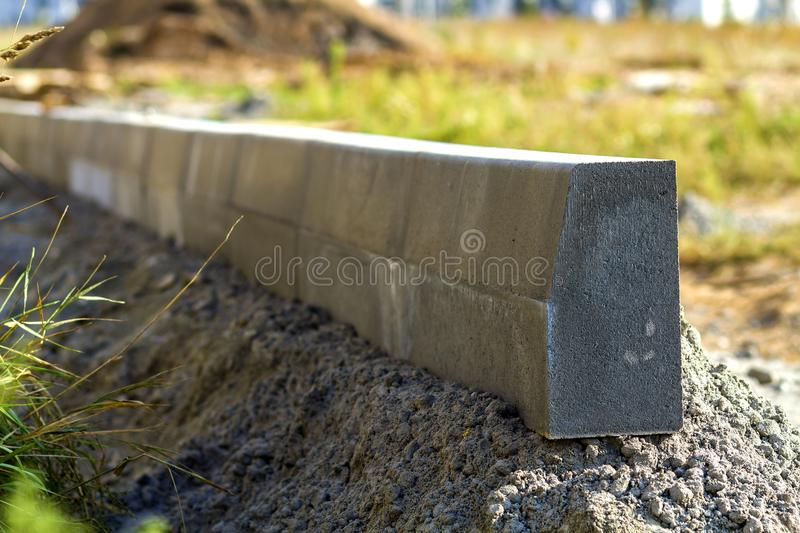 Concrete curb installation works at road construction site. Shallow DOF. royalty free stock photography