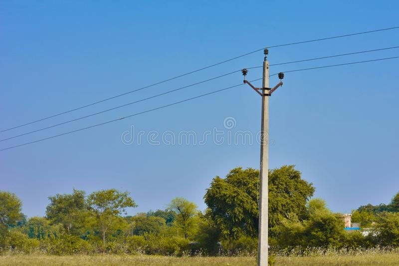 Concrete electric poles in a field under the beautiful blue sky. stock photo