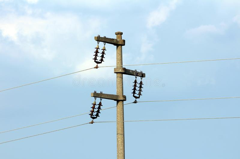 Concrete electrical power line utility pole with ceramic insulators and three connected wires stock image