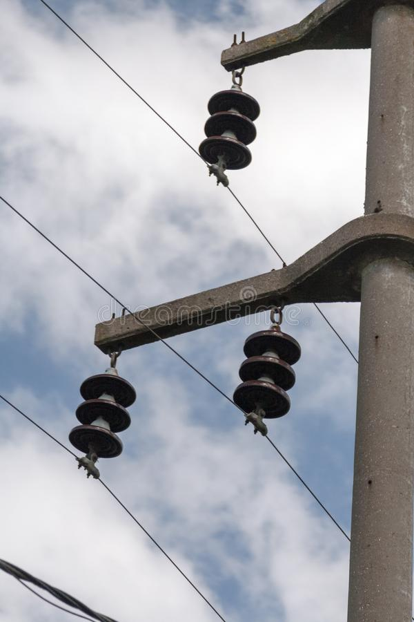 Concrete electrical power line utility pole with ceramic insulators and three connected wires.. royalty free stock photos
