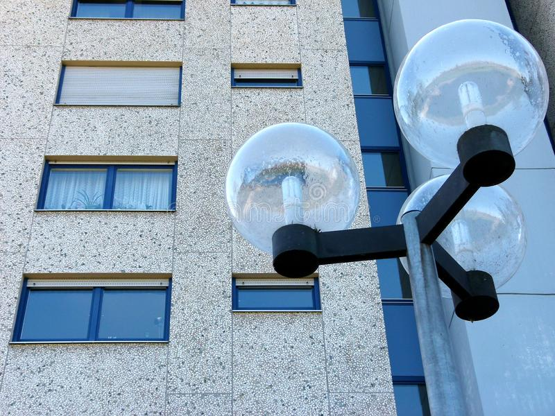 Concrete facade of a high-rise building with modern street lamp. Modern living, anonymous living, concrete facade with windows, street lamp with glass balls stock photo