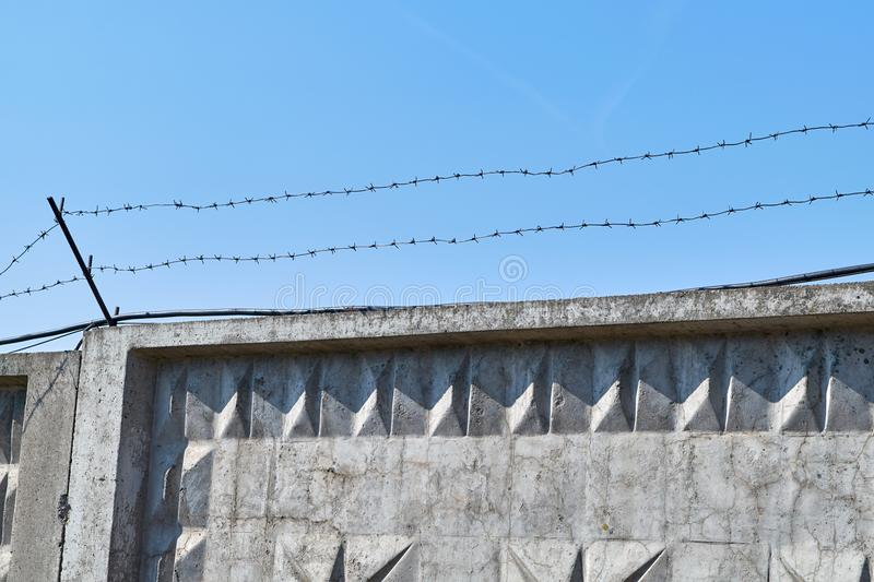 Concrete fence with barbed wire on blue sky background. Barbed wire is fixed on top with metal rods. Restricted area. Passage is prohibited. Restriction of royalty free stock photos