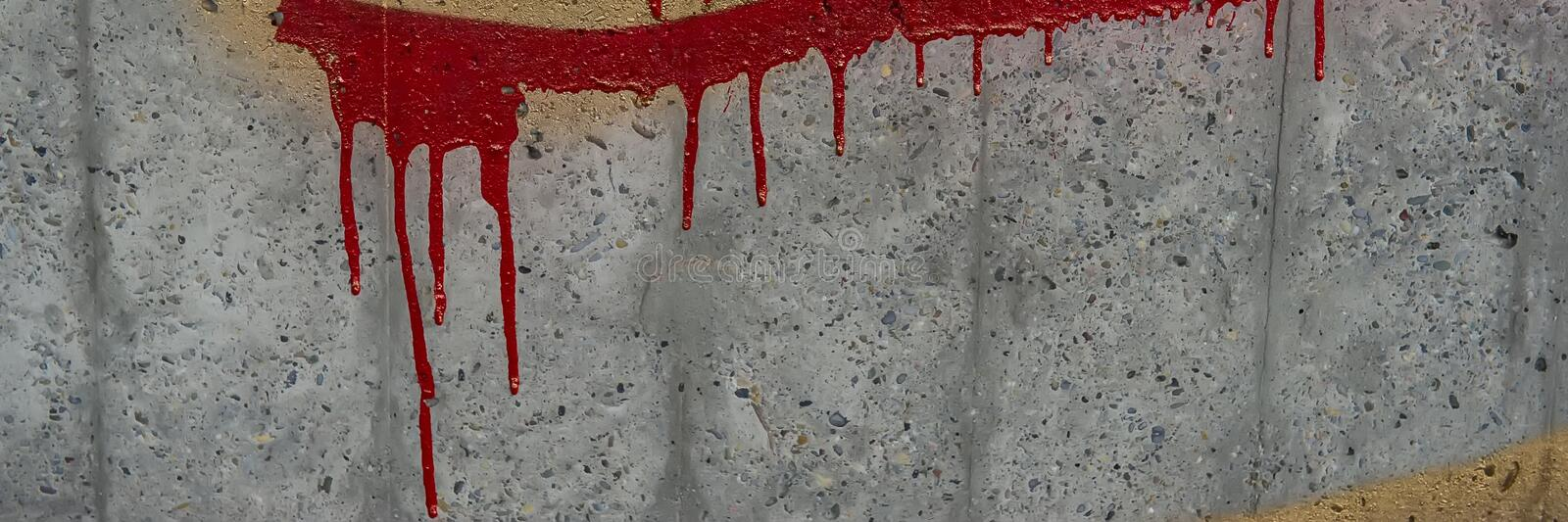 Concrete fence with traces of spilled red paint royalty free stock photos